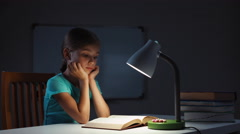 Child reading a book in the night Stock Footage