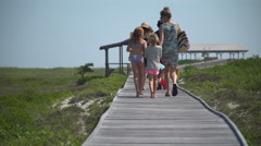Rear view of family walking out to Ho Hum beach on Fire Island Stock Footage