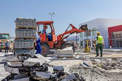 Forklift is carry vibration plate compactor machine at building site Stock Photos