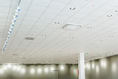 Modern office ceiling with air duct and lamps Stock Photos