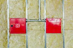 Both side of red fire hydrant cabinet in unfinished dividing wall - stock photo