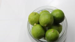 Green Limes rotating in a glass container - stock footage