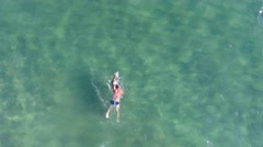 A man swims in the sea. Aerial view from copter Stock Footage
