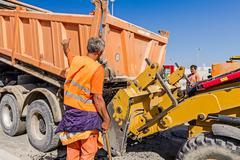 Truck dumper is pouring hot asphalt into bulldozer scoop Stock Photos