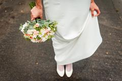 Beautiful wedding bouquet in hands of the bride - stock photo