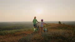 Steadicam shot: Mom and daughter walk together in the sunset, are bicycles Stock Footage