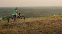 Steadicam shot: A young woman leads a bike through the hills, scenic landscape Stock Footage