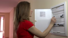Long-haired woman turning on light-switch at power control panel at home Stock Footage