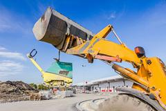 Moving vibration plate machine with excavator Stock Photos