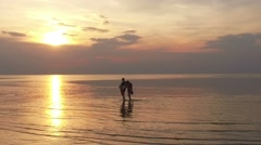 Young couple walking on the water along Summer Beach at Sunset Stock Footage