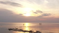 Group of friends swimming in the sea at sunset running into water getting wet Stock Footage