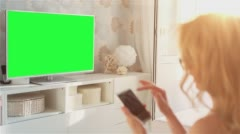 Beautiful Young Woman Using SmartPhone In Front Of The TV with Green Screen 1 Stock Footage