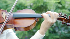 Violinist playing the violin outdoors. Summer green leaves backgound. 4K Stock Footage