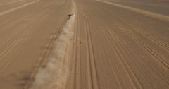 High angle drone footage of off-road vehicle moving through arid landscape, Erg Stock Footage