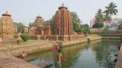 People bath in lake at Mukteswar Hindu temple,Bhubaneswar,India Stock Footage