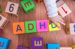 ADHD concept. Baby is playing with cubes with letters. Stock Photos