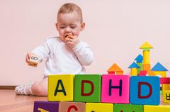 ADHD concept. Baby is playing with colorful cubes with letters. Stock Photos