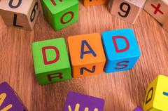 Dad word written with colorful cubes with letters. Stock Photos