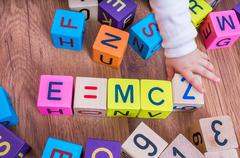 Genius baby with high IQ is playing with cubes and writing formulas. Stock Photos