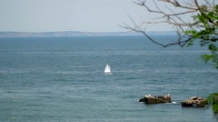 The yacht floating in the sea. On the far bank can be seen the city. - stock footage