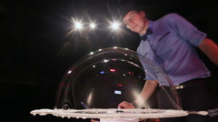 The man the actor blows big a soap bubble on a table. Soap bubbles show Stock Footage