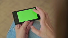 Pretty woman holding smart phone with green screen display and touching Stock Footage