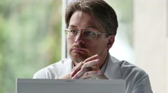 Portrait Of Serious Male Doctor Using Computer In Clinic Stock Footage