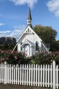 Old wooden church with picket fence - stock photo