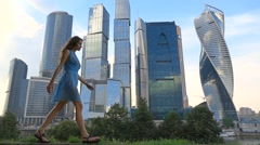 Slim girl in blue dress walking against modern skyscrapers, super slow motion Stock Footage