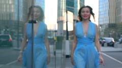 Cheerful brunette girl in blue dress walking towards camera on the street, super - stock footage