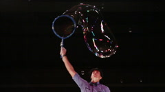 The man the actor creates a big soap bubble and lifts him by means of hands up Stock Footage