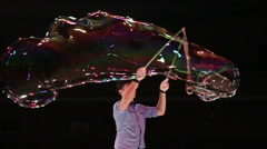 The man the actor creates a huge long soap bubble by means of a rope. Soap Stock Footage
