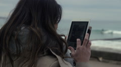 Female using a iPad at the beach to take a photo Stock Footage