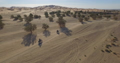 High angle drone footage of people riding motorcycles, Erg Chebbi, Morocco Stock Footage
