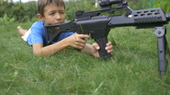 Boy lying on the grass shoots from a sniper rifle, the boy plays in the war Stock Footage