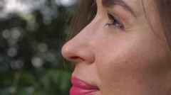 Pretty brunette girl looking at skysrapers from the park, 4K pan and zoom out Stock Footage