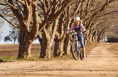 Young girl riding her bicycle bike down dirt road tree lined avenue Stock Photos