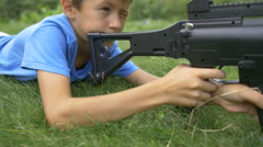 Boy shoots from a sniper rifle, the boy plays in the war Stock Footage