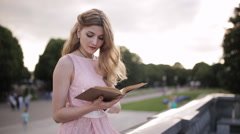 Young attractive girl reading a book with an interest in a summer park Stock Footage