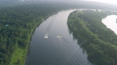 Aerial tilt shot of two motorboats cruising along the river Stock Footage