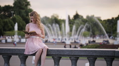 Young attractive girl in a summer park fountain reads a book with interest Stock Footage