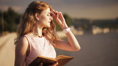 Cute little girl with book in hand straightens the hair at sunset promenade Stock Footage