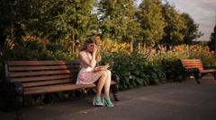 Beautiful young blond woman sitting on a bench in the summer park and reading a Stock Footage