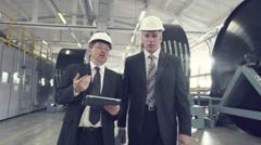 Two businessmen walking through factory Stock Footage