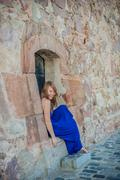 Girl sits in an old wall Stock Photos