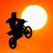 silhouette of motocross rider jump in the sky at sunset - stock illustration