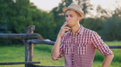 A young man in a hat smokes a fence. He is a farmer in the countryside Stock Footage