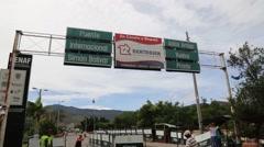 Downward Tilt Shot of Border Sign and Woman Carrying Bag Across Border Stock Footage