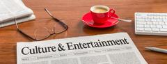 A newspaper on a wooden desk - Culture and Entertainment Stock Photos