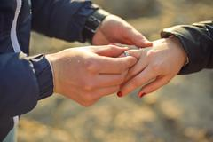 Man wears a wedding ring on woman's hand Stock Photos
